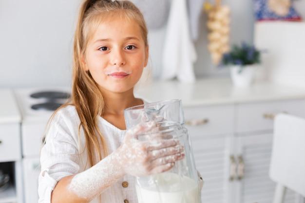 Adorável menina segurando um copo de leite