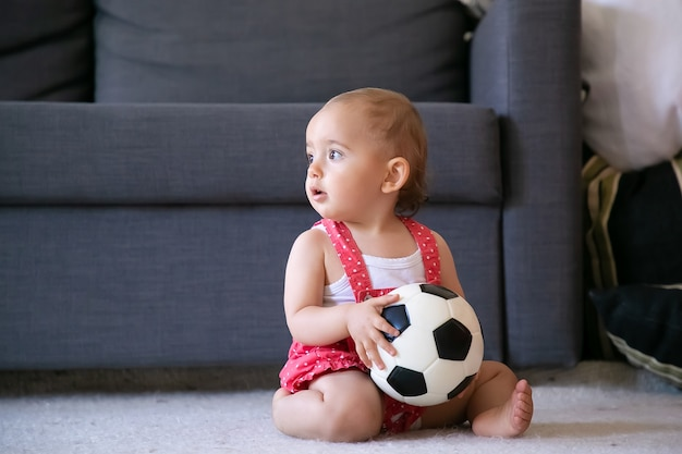Adorável menina segurando uma bola de futebol, sentada no tapete com os pés descalços e olhando para longe. infantil fofo em shorts de macacão vermelho, jogando em casa sozinho. conceito de férias, fim de semana e infância