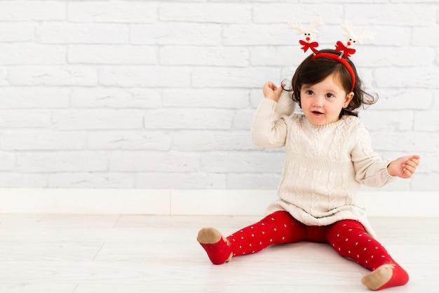 Adorável menina sentada ao lado da parede de tijolo