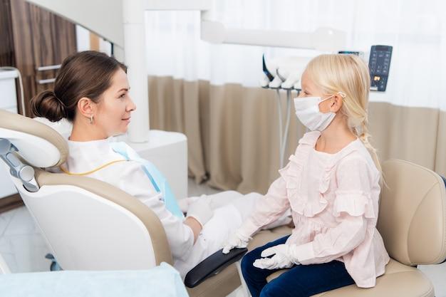 Adorável menina sentada e fazendo um exame de uma médica, o médico está sentado em uma cadeira de dentista.