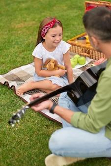 Adorável menina sentada em uma grama verde no parque e olhando para o pai tocando violão
