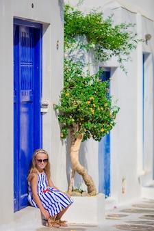 Adorável menina sentada na frente da porta azul ao ar livre na aldeia tradicional grega típica em mykonos na grécia