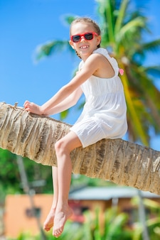 Adorável menina sentada na palmeira durante as férias de verão na praia branca