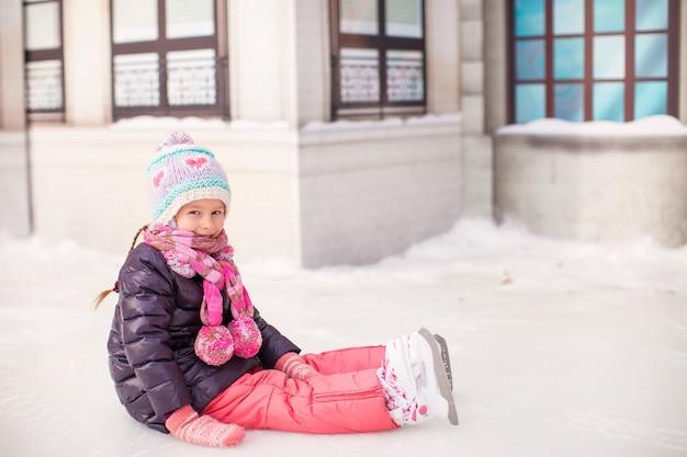 Adorável menina sentada no gelo com patins após a queda