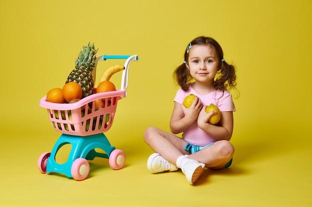 Adorável menina sentada perto de um carrinho de compras cheio de frutas, segurando dois limões nas mãos e fofo sorrindo para a câmera. isolado em amarelo com espaço de cópia.