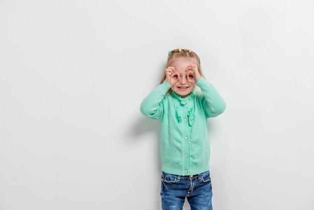 Adorável menina simulando óculos com as mãos