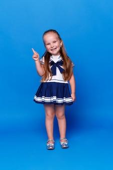 Adorável menina sorridente apontando o dedo para cima