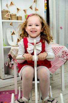 Adorável menina sorridente no cavalo de madeira do brinquedo no interior de um quarto de criança.