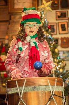 Adorável menina tocando tambor