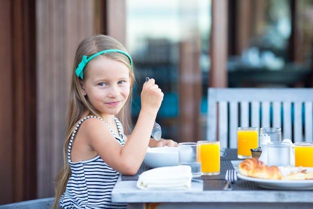 Adorável menina tomando café da manhã no café ao ar livre