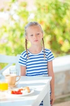 Adorável menina tomando café da manhã no café com vista para o mar no início da manhã