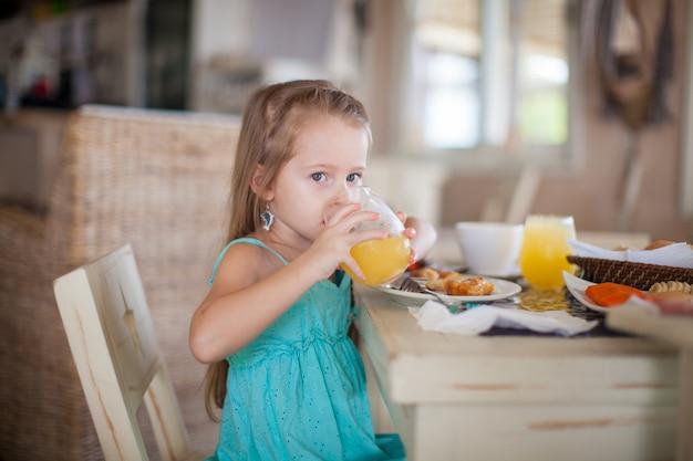 Adorável menina tomando café da manhã no restaurante do resort