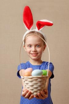 Adorável menina usando orelhas de coelho, brincando com ovos de páscoa