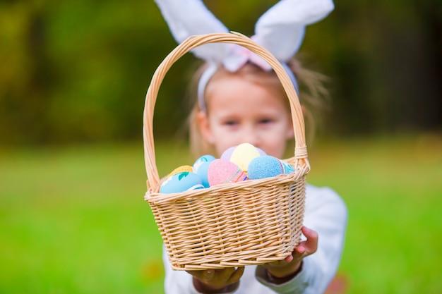 Adorável menina usando orelhas de coelho com uma cesta cheia de ovos de páscoa na primavera ao ar livre