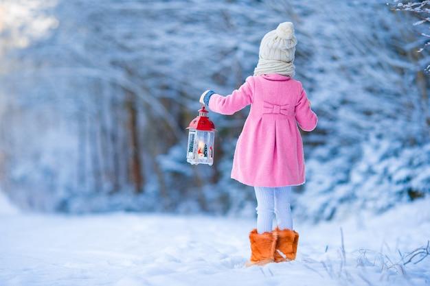 Adorável menina vestindo casaco quente ao ar livre no dia de natal segurando a lanterna