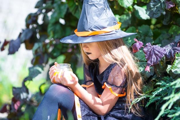 Adorável menina vestindo fantasia de bruxa com vassoura no dia das bruxas ao ar livre