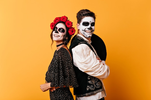 Adorável menina zumbi em coroa de flores rosa posando na parede amarela. casal feliz com maquiagem muerte se divertindo no halloween.