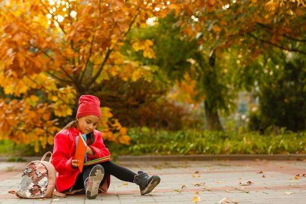 Adorável menininha estudando ao ar livre no dia de outono brilhante