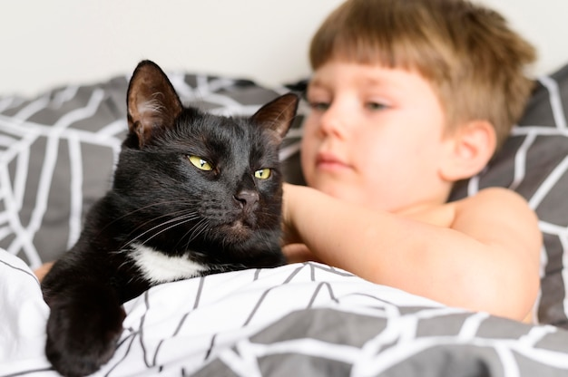 Adorável menino acariciando seu gato