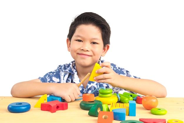 Adorável menino asiático é jogar brinquedo colorido bloco de madeira