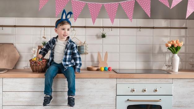 Adorável menino com orelhas de coelho, olhando para longe