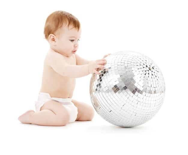 Adorável menino com uma grande bola de discoteca sobre o branco