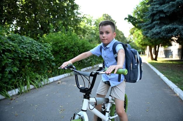 Adorável menino de bicicleta indo para o estabelecimento da escola. crianças andando de bicicleta, crianças andando de bicicleta