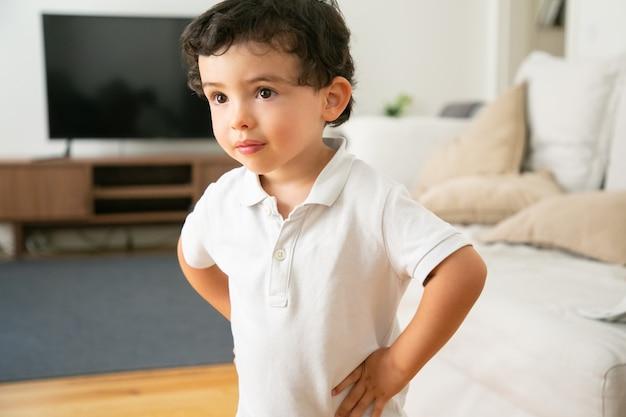 Adorável menino de camisa branca em pé com as mãos nos quadris na sala de estar
