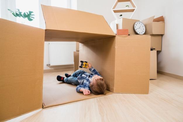 Adorável menino deitado na caixa de papelão, brincando com o carro de brinquedo em casa