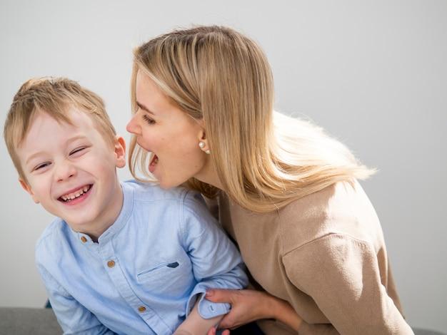Adorável menino e mãe tocando juntos