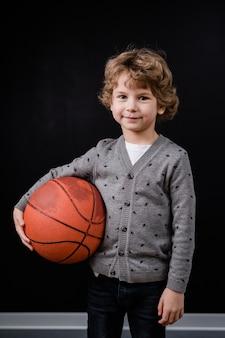 Adorável menino em trajes casuais segurando uma bola para jogar basquete isolado