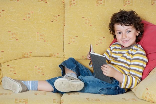 Adorável menino feliz lendo na poltrona da sua casa