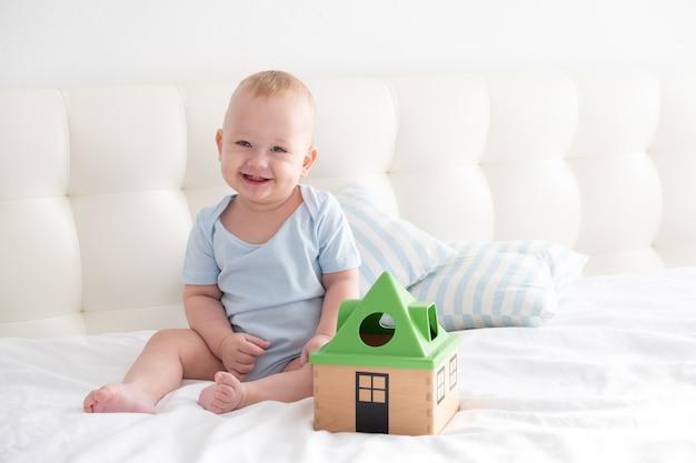 Adorável menino feliz sentado na cama brincando com um classificador de brinquedos