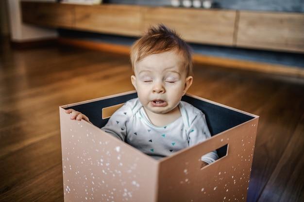 Adorável menino loiro caucasiano sentado na caixa e espirrando. interior da casa.