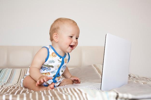 Adorável menino loiro sentado na cama olhando para o laptop