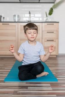 Adorável menino meditando em casa