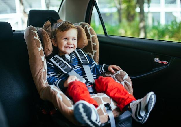 Adorável menino na cadeira de segurança.