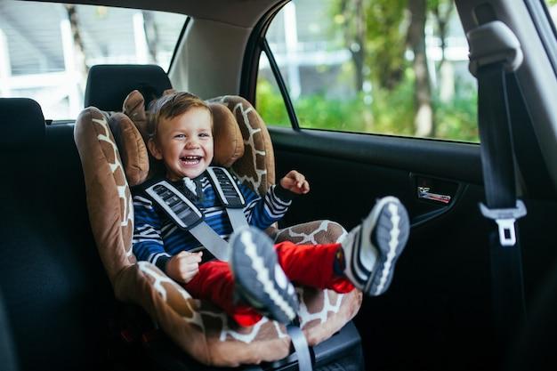 Adorável menino na cadeirinha de segurança.