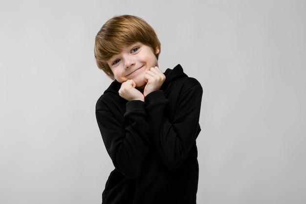 Adorável menino sorridente em pé com as mãos perto do rosto