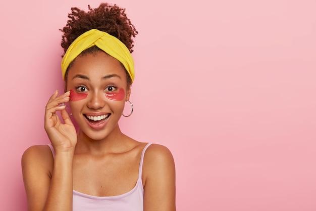 Adorável modelo de pele escura com cabelo crespo, aplica adesivos de hidrogel rosa sob os olhos para remover bolsas e inchaço após uma noite sem dormir, tem expressão alegre, vestido casualmente
