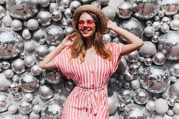 Adorável modelo feminino com chapéu de palha vintage posando perto de bolas de discoteca. mulher loira relaxada em um elegante vestido listrado arrepiante
