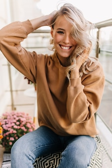 Adorável modelo feminino posando na manhã de fim de semana. retrato de menina bem-humorada tocando seu cabelo loiro.