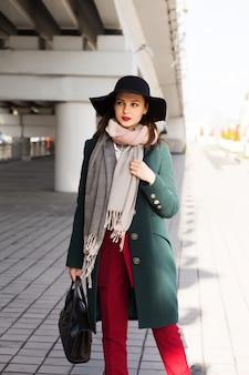 Adorável modelo morena de casaco verde e chapéu preto posando para a cidade