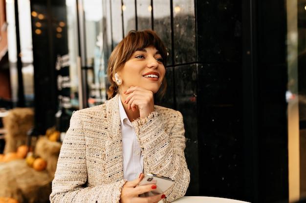Adorável mulher adorável em roupas da moda sentada em um café ao ar livre, usando o smartphone e esperando por amigos no fundo das luzes da cidade