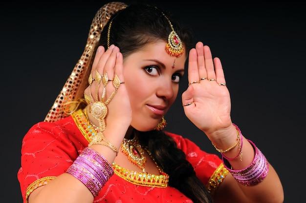 Adorável mulher adulta branca caucasiana em traje indiano levanta as mãos. retrato feminino em fundo escuro