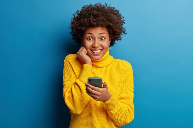 Adorável mulher adulta de pele escura vestida com um macacão amarelo usando um telefone celular com uma expressão feliz