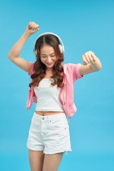 Adorável mulher asiática cantando e se divertindo enquanto ouve música usando fones de ouvido sem fio isolados sobre fundo azul
