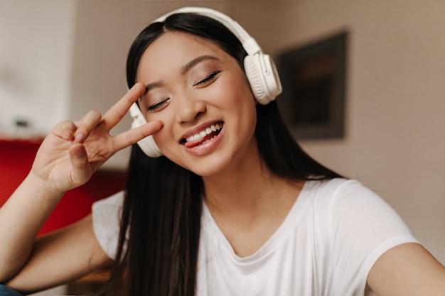 Adorável mulher asiática com top branco e fones de ouvido mostra a língua, o símbolo da paz e poses com os olhos fechados