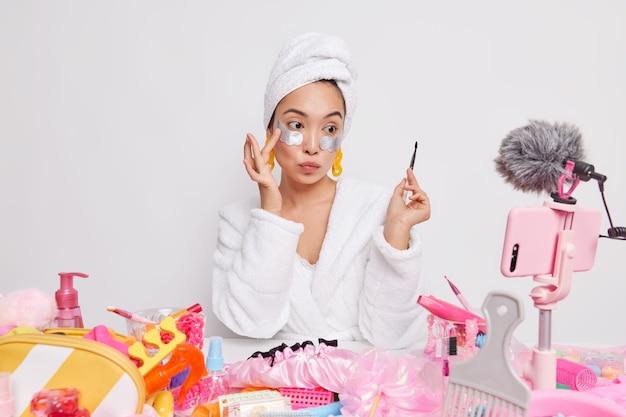 Adorável mulher asiática mdel com escova profissional coloca adesivos sob os olhos usa ferramentas para maquiagem grava vídeo blog para sites de redes sociais dá conselhos de beleza e cuidados com a pele