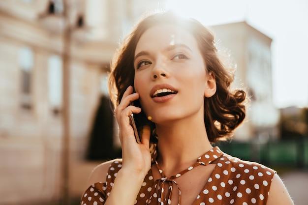 Adorável mulher branca ligando para alguém enquanto caminhava pela cidade. tiro ao ar livre da sonhadora garota caucasiana em pé na rua com o celular.